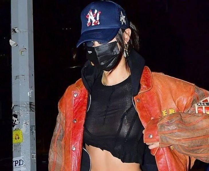 Модель в маске демонстрирует свою грудь в прозрачном топе